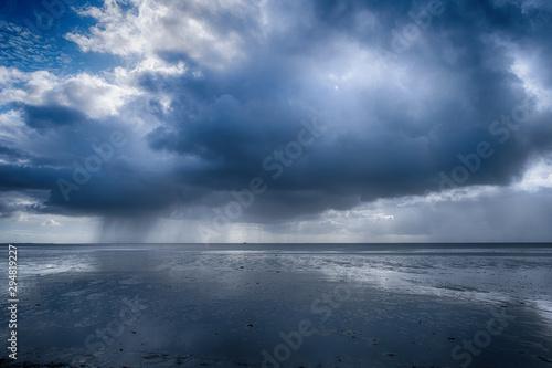 Vászonkép  Regenwolken über dem Wattenmeer vor Pellworm/Deutschland bei Ebbe
