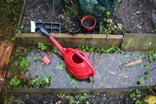 Close Up Of Flooded Allotment Garden After Heavy Rainfall With Red Watering Can And Pots In Raised Wood Organic Vegetable Bed With Flood Of Rain Water Pool And Seed Tray Green Plants On Earth Soil