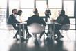Leinwanddruck Bild - Background concept with business people sitting at the meeting table in the office near a window glass