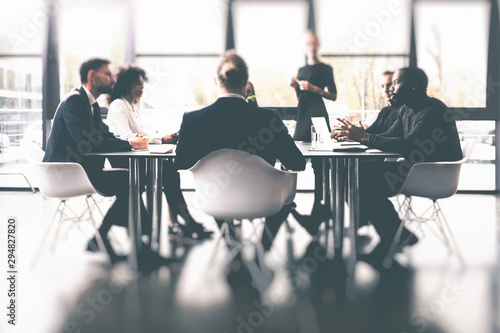 Obraz Background concept with business people sitting at the meeting table in the office near a window glass - fototapety do salonu