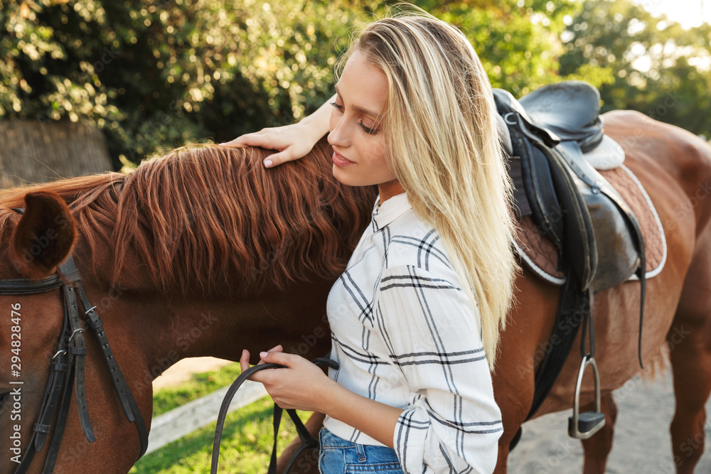 Fototapety, obrazy: Beautiful smiling young blonde woman petting a horse at the stable