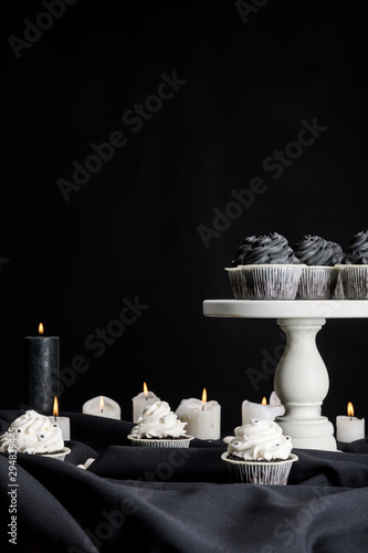 tasty Halloween cupcakes with black cream on white stand near burning candles isolated on black