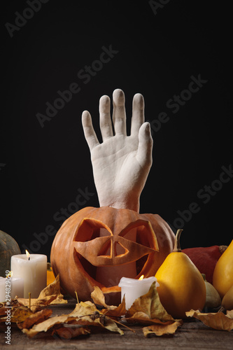 dry foliage, burning candles, decorative hand in carved Halloween pumpkin on wooden rustic table isolated on black