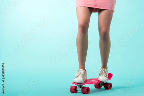 cropped view of girl in pink outfit standing on penny board on turquoise background