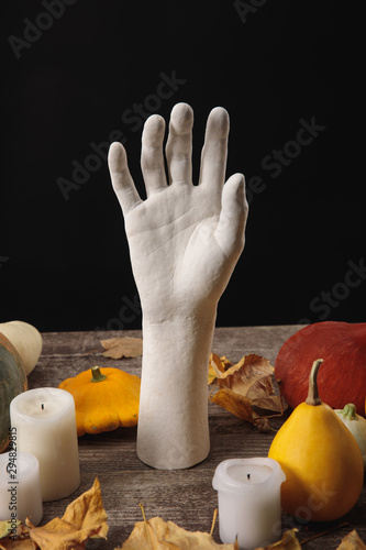 dry foliage, candles, ripe pumpkins and decorative hand on wooden rustic table isolated on black