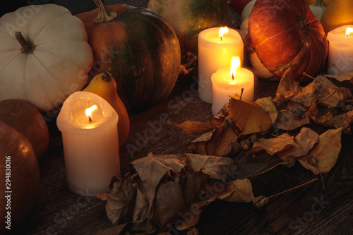 dry foliage, burning candles, ripe pumpkin on wooden rustic table
