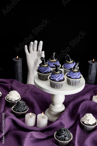 tasty Halloween cupcakes on white stand near burning candles and decorative hand on purple cloth isolated on black