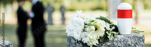 Fotomural  panoramic shot of white flowers and cemetery urn on tombstone