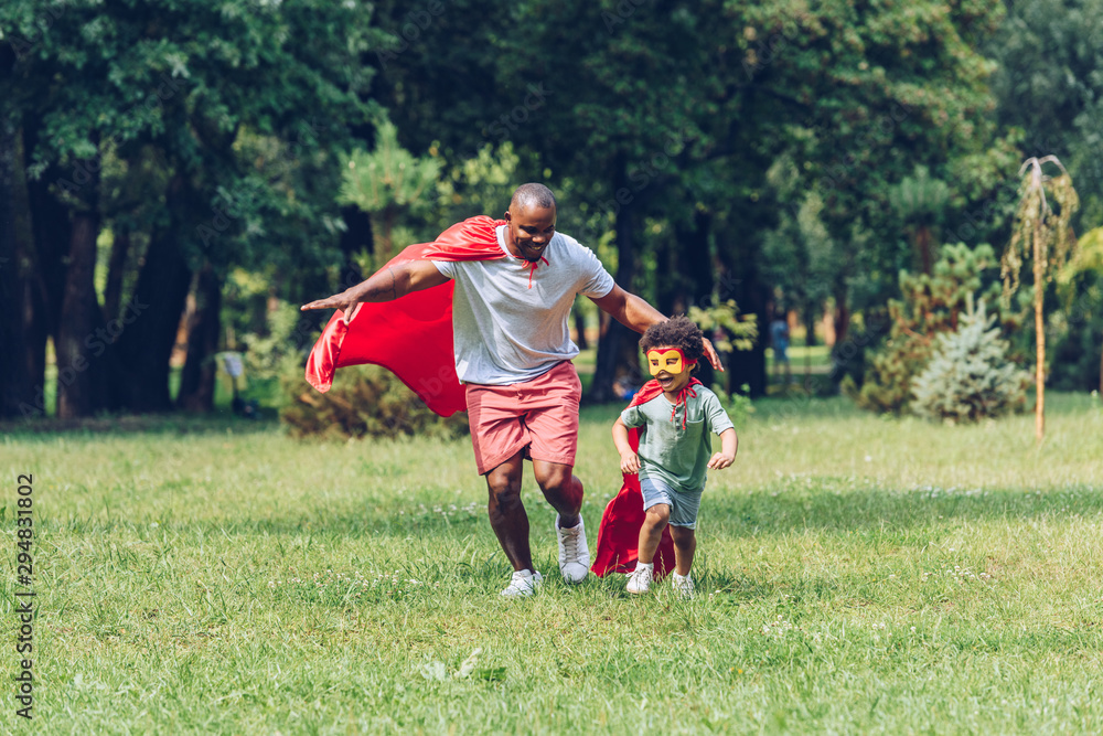 Fototapeta happy african american father and son running in costumes of superheroes in park