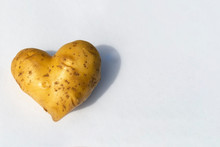 Potatoes In The Shape Of A Heart On A White Background. Expression Of Love With Vegetables, Potato Lovers. Place For Text, Copy Space.