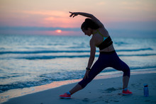 Healthy Woman On Beach In Evening Stretching