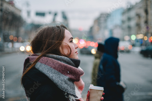 Photo  Woman with disposable cup in warm clothing crossing city street in winter