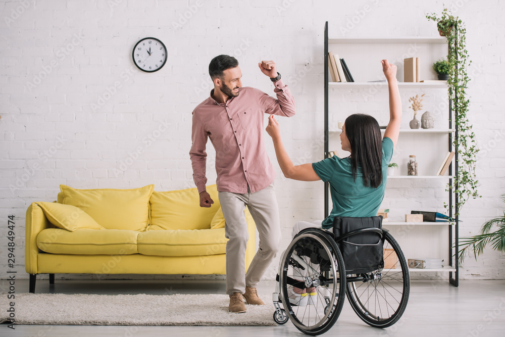 Fototapety, obrazy: back view of young disabled woman in wheelchair dancing with happy boyfriend