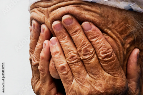 Obraz na plátne  An old saddened grandmother closes her tearful eyes with wrinkled palms close-up
