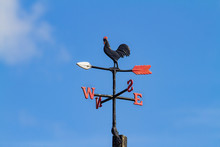 Cockerel Rooster Weather Vane, Wind Vane, Weathercock Against Blue Sky. Wind Direction Instrument, With Letters For Compass Points, Painted Black Red And White.