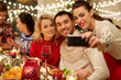 canvas print picture - holidays and celebration concept - happy friends having christmas dinner at home and taking selfie by smartphone
