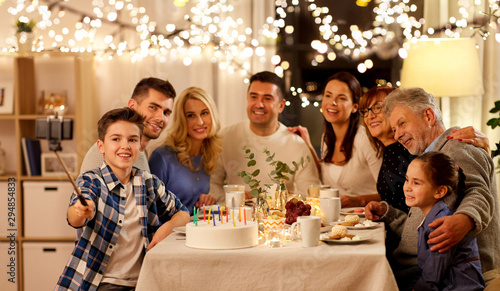 Fototapety, obrazy: celebration, holidays and people concept - happy family having birthday tea party at home and taking picture by smartphone on selfie stick