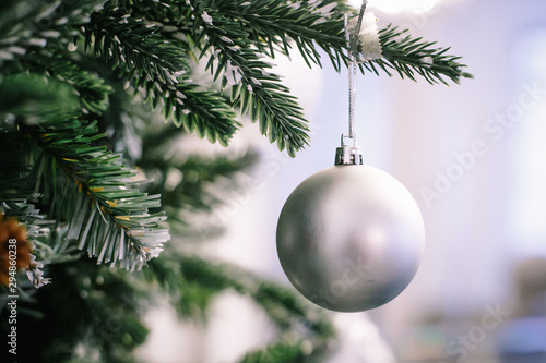 Fototapeta Christmas tree branch decorated with silver balls and white decor obraz