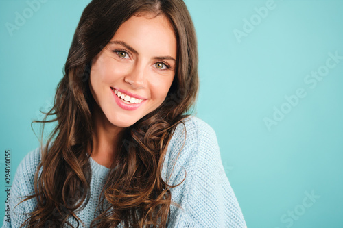 Fotografía  Portrait of gorgeous smiling girl in sweater happily looking in camera over blue