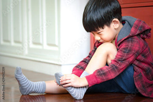 Happy and adorable little preschool Asian boy puts on socks, gets ready for school Fototapet