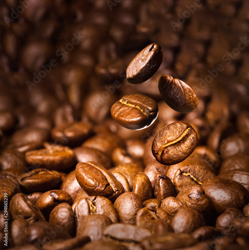 Wall Murals Cafe Roasted coffee beans. Seeds of freshly roasted coffee with smoke. Coffee beans closeup with emphasis on the grain with smoke.