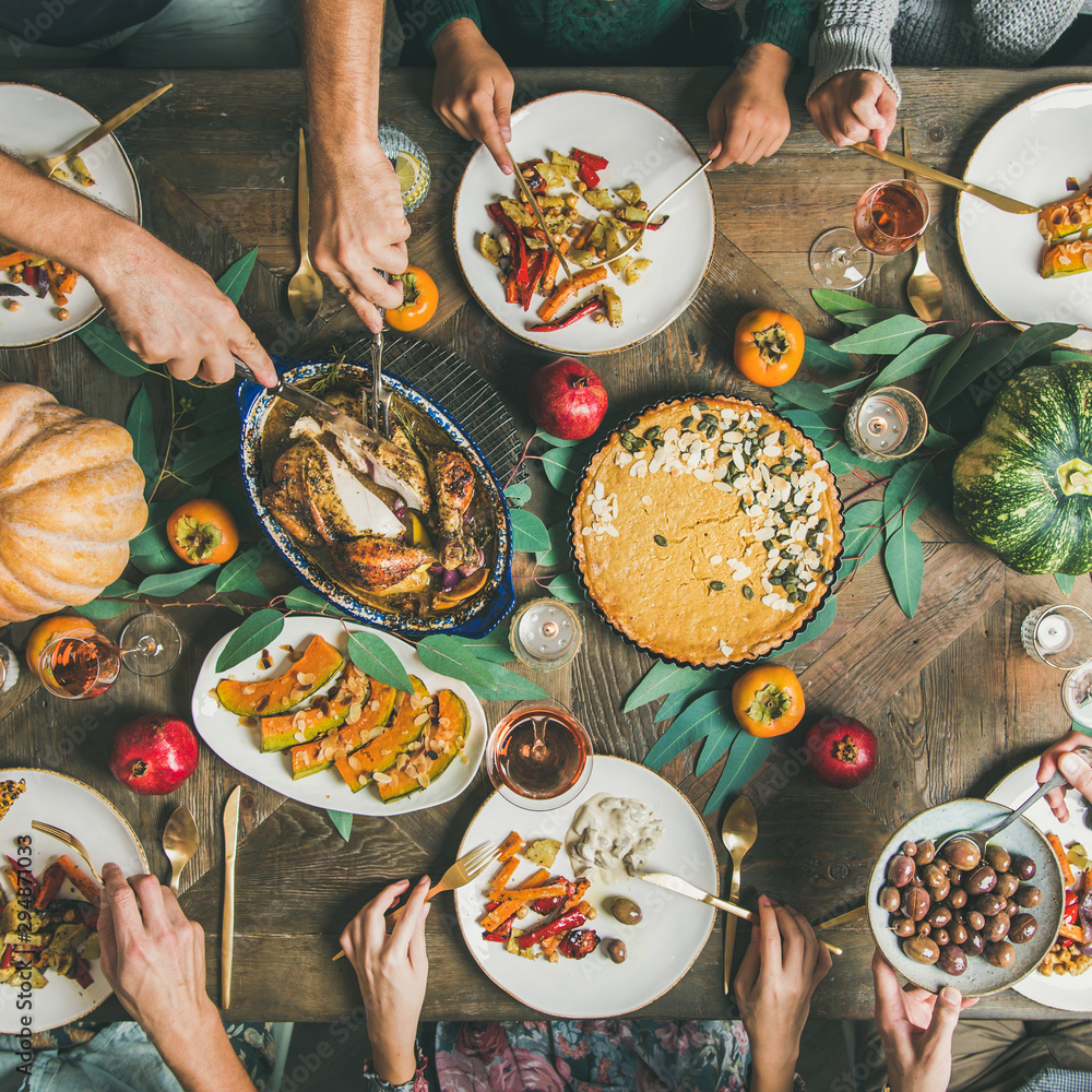 Fototapeta Thanksgiving or Friendsgiving holiday celebration party. Flat-lay of friends feasting at Thanksgiving Day table with turkey, pumpkin pie, roasted vegetables, fruit and rose wine, top view, square crop