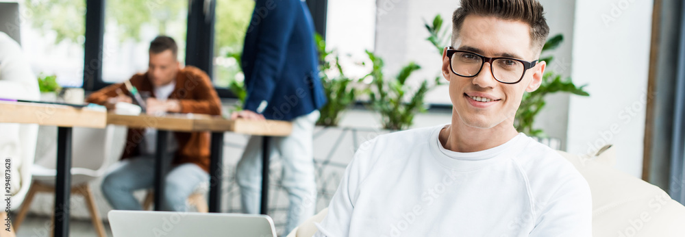 Fototapeta panoramic shot of young businessman in glasses using laptop and smiling at camera near colleagues working in office