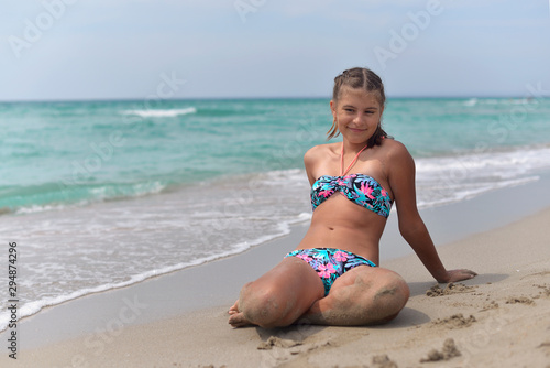 Obraz Teenage girl lying on the sandy beach on a hot summer day - fototapety do salonu