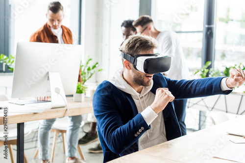 Fototapety, obrazy: young businessman imitating fight while using vr headset, and multicultural colleagues working in office