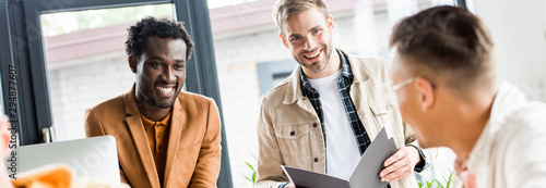 Photographie  panoramic shot of young multicultural businessmen talking and smiling in office