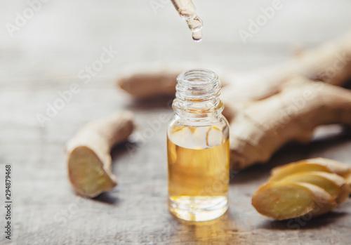 Fototapeta Ginger essential oil in a small bottle. Selective focus. obraz