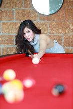 Young Beautiful Asian Woman Playing And Aiming For Billiards Ball On Red Pool Table In Club