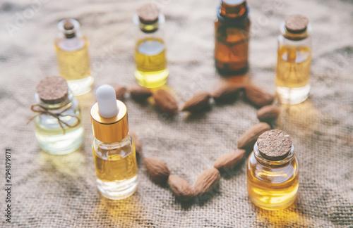 Fototapeta Almond essential oil in a small bottle. Selective focus. obraz