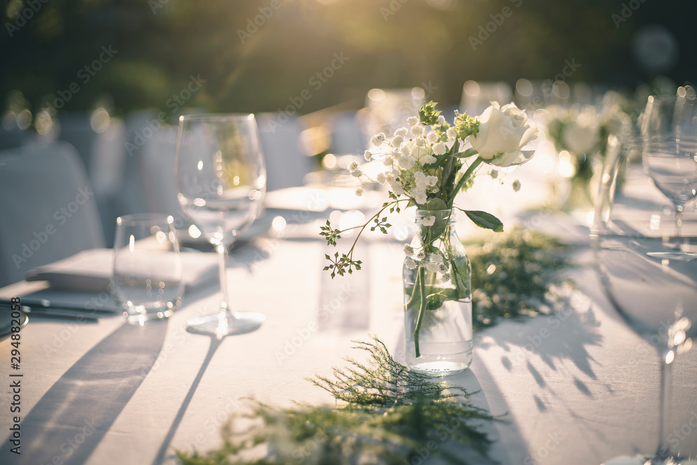 Fototapeta Beautiful outdoor table setting with white flowers for a dinner, wedding reception or other festive event.