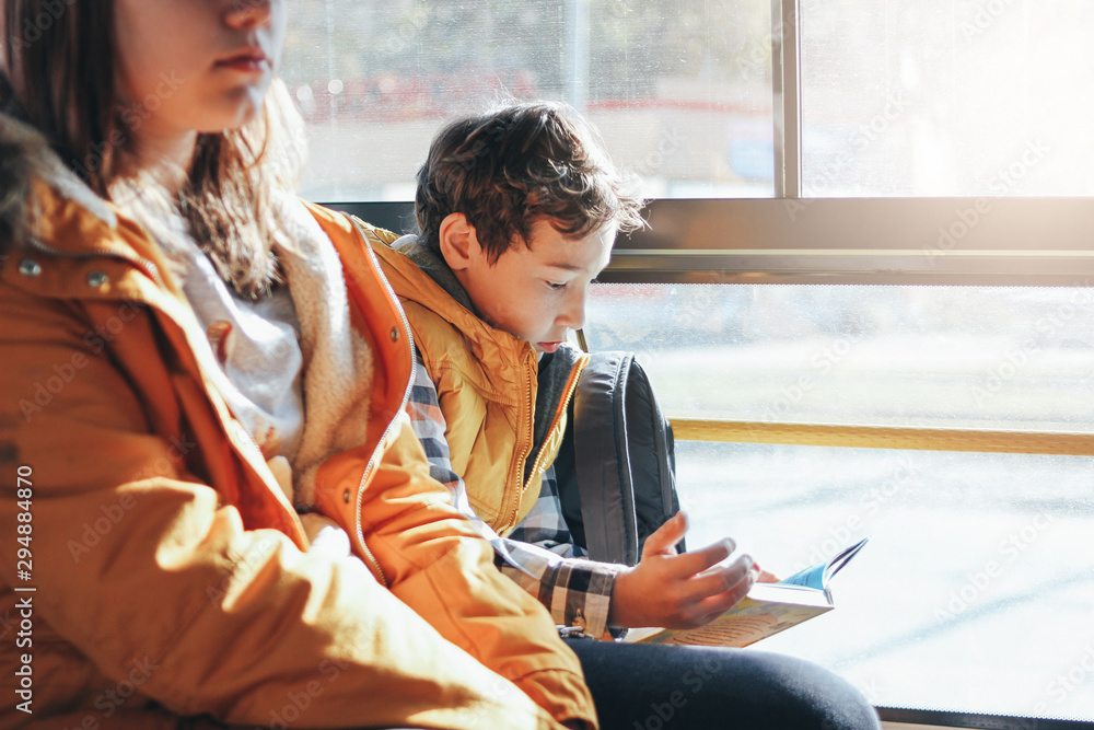 Fototapety, obrazy: Children students in yellow jackets riding in the city bus. School boy reading book at the window