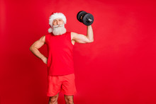 Portrait Of Confident Santa Claus In Nicholas Hat Cap Holding Dumb Bell So Proud About Himself Wearing Sport Wear Isolated Over Red Background