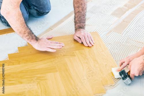 Fototapeta Handwerker verlegt Parkettboden , fischgrätparkett boden.  obraz na płótnie