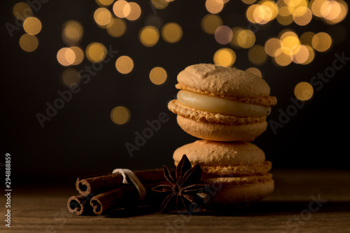 Fotobehang Macarons Macarons Christmas style, Beautiful Stack of Macarons with cinnamon and aniseed , isolated on bokeh lights black background , copy space