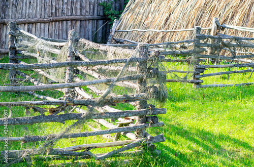 Foto auf AluDibond Lime grun thatched roof hut with a wooden fence by the river