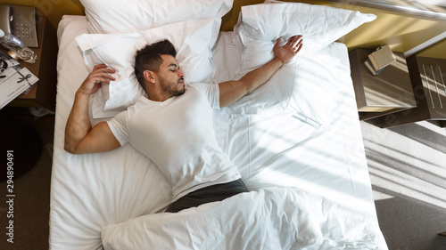 Young man sleeping in bed, staying in hotel Wallpaper Mural