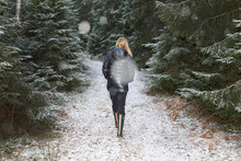 Young Woman Walking On A Snowy Path Through A Forest