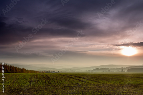 Photo  View of the Ore Mountains in autuum, foggy meadow in the background and forests,