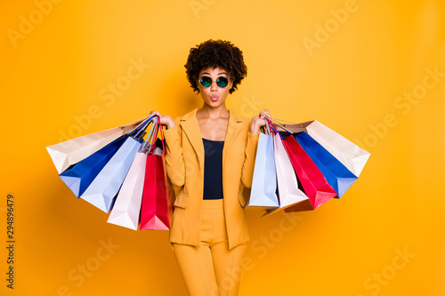 Portrait of funny funky brunette wavy hair afro american lady on leisure travel hold bags shopping purchase addicted person wear style sunglass outfit pants trousers isolated yellow color background