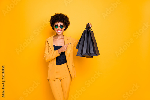 Look real bargain. Portrait of positive brunette curly hair afro american girl hold black bags point index finger show what she shopped bought wear style pants outfit isolated yellow color background