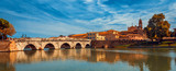 Tiberius bridge in Rimini on a background of blue sky with white clouds