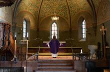 Priest In Purple Robes Standin...