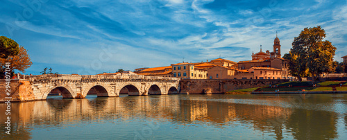 Foto auf Leinwand Brücken Tiberius bridge in Rimini on a background of blue sky with white clouds