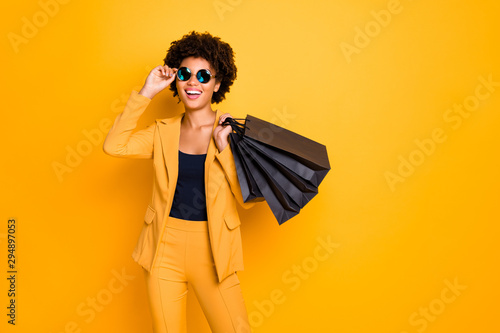 Portrait of positive cheerful afro american girl have fun on free time hold black bags addicted shopper want shop all bargains wear style outfit pants trousers isolated over yellow color background