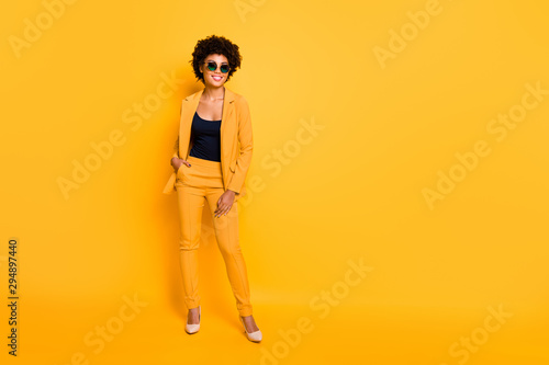 Poster Hoogte schaal Full length photo of positive cheerful afro american have rest relax feel fun dream dreamy put hands in trousers wear stylish suit high-heels isolated over yellow color background
