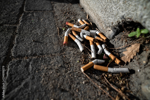 Photo  Cigarettes Butts on sidewalk pavement - Cigarettes addiction dirty background